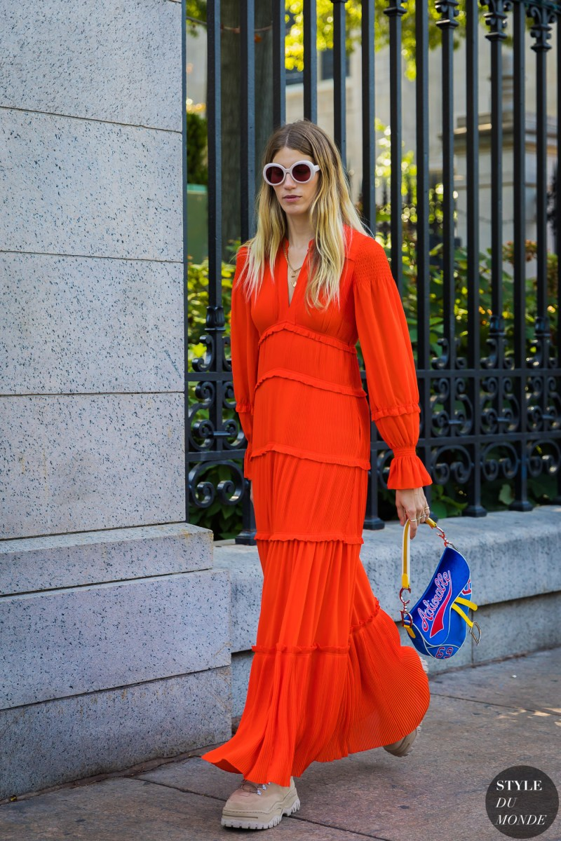 street style shot of veronika heilbrunner in bright orange red dress, dior vintage sadle bag and timbs