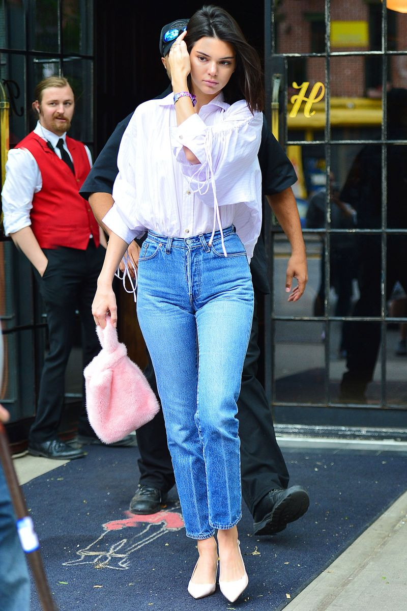 Kendal Jenner holds pink fur tote. She is wearing a white top and blue jeans