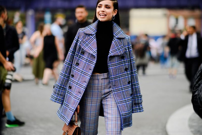 Street style of girl wearing a plaid jacket and pants with black turtle neck