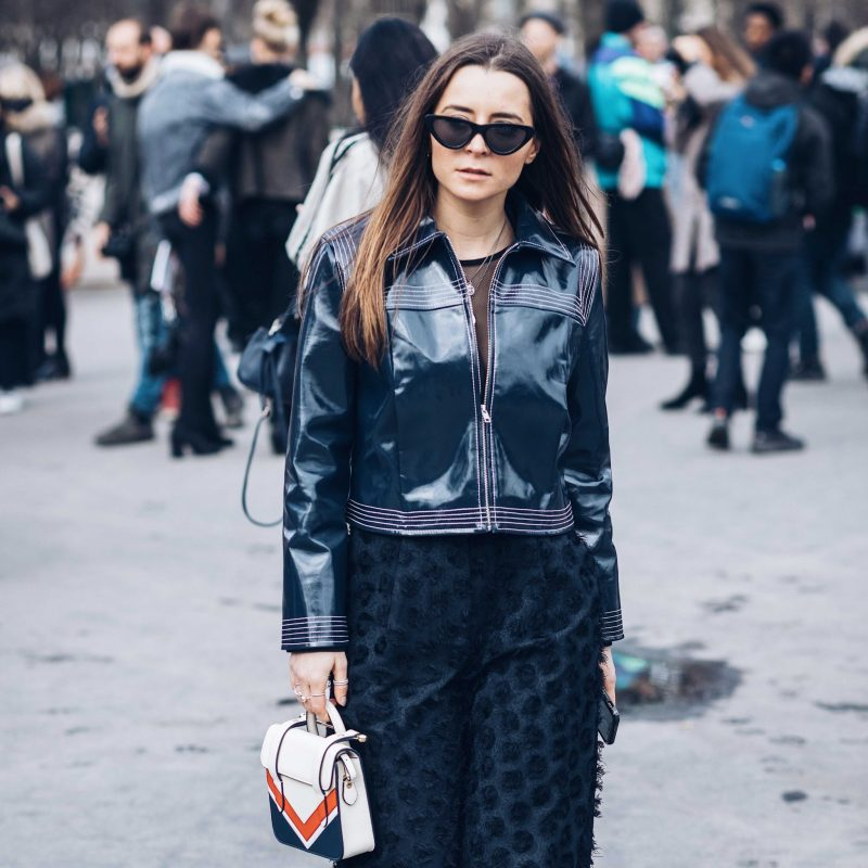 Street style shot of woman in patent blue jacket