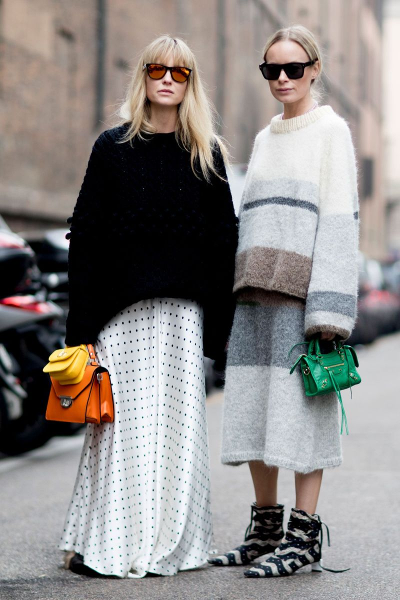 street style shot of two women wearing sweaters, skirts and carrying mini bags