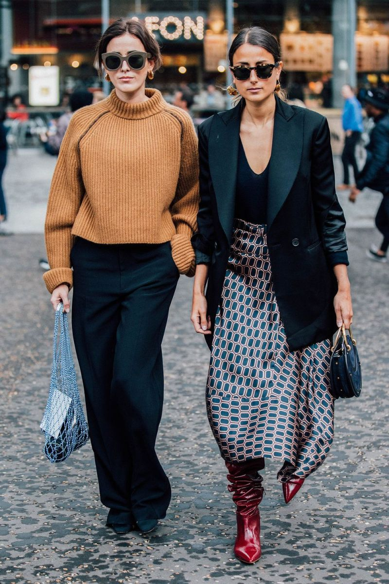 Two street style women seen crossing the street at new york fashion week wearing fall attire.