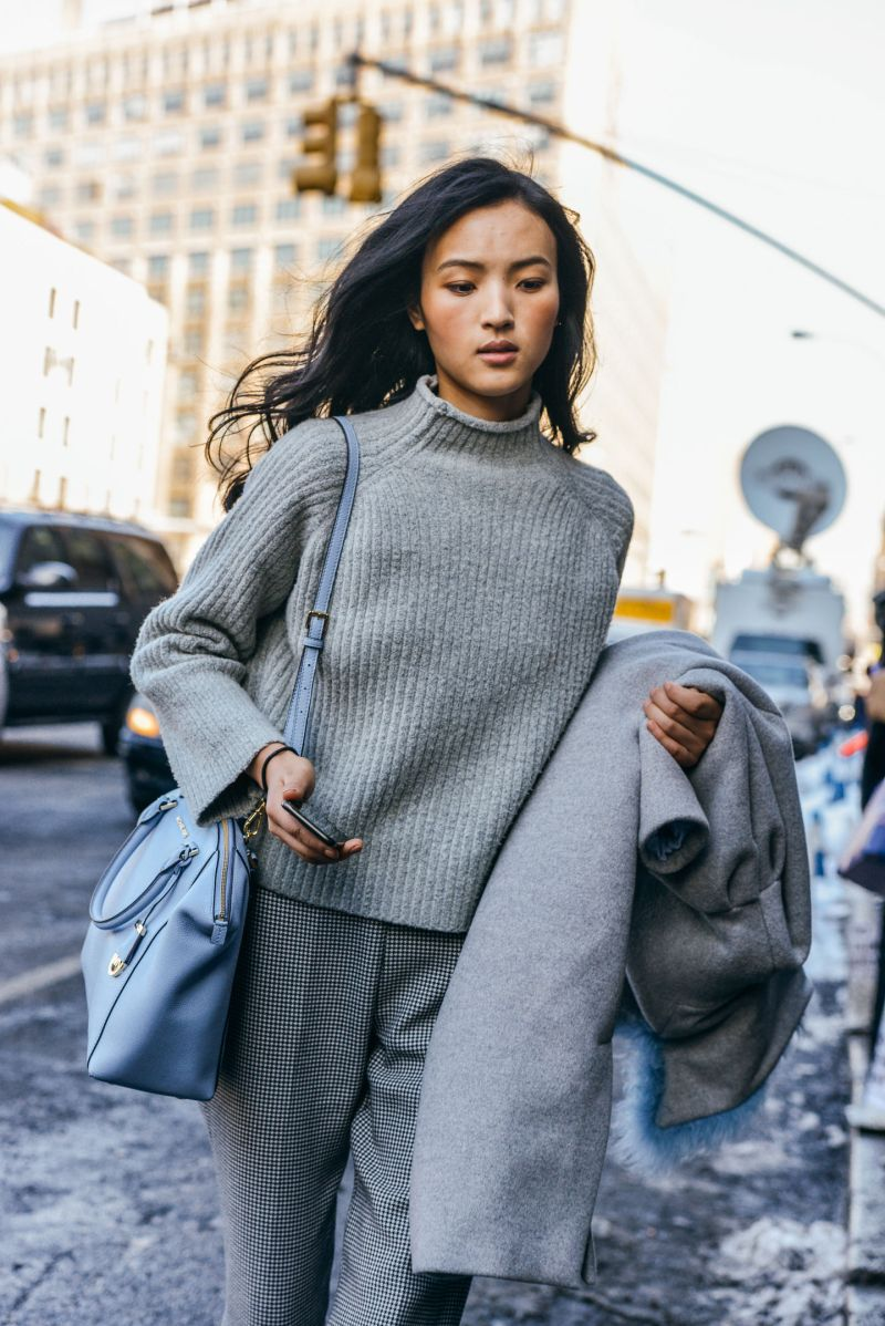 Street style shot of girl wearing grey mockneck sweater, grey pants and blue purse.