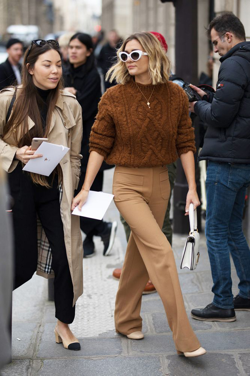 Street style shot of girl wearing a brown cable knit crew neck sweater and tan pants
