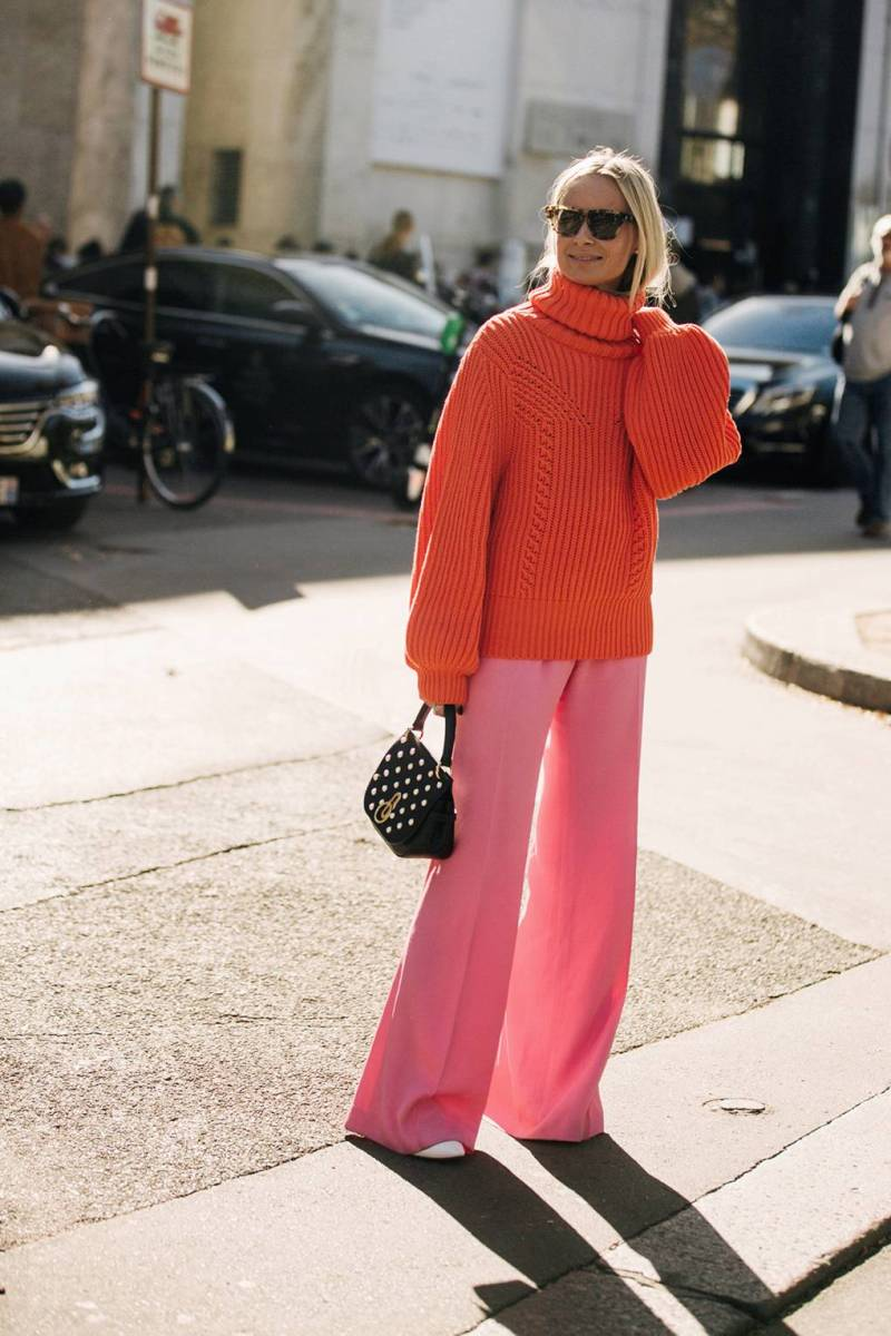 Street style shot of girl wearing pink pants and orange sweater