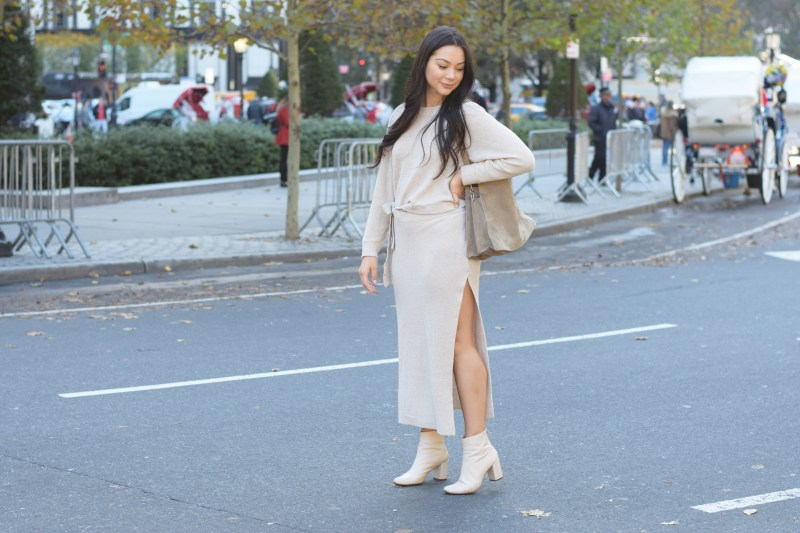 Ana Szumilas wearing a neutral knit skirt and sweater set walking across the street in new york city