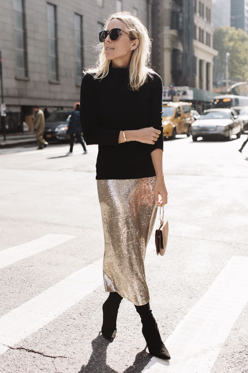 Woman in a black sweater, silver midi skirt, metallic booties and carrying a handbag