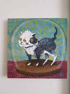 black and white cat with three eyes in a clear globe on a red floor, yellow and teal background