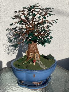 a brown tree with a door and steps on/infront of the trunk with green leaves in a blue pot
