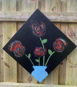 red roses in blue vase on a diamond shaped black background