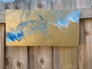 gold and blue drip painting hung on a fence