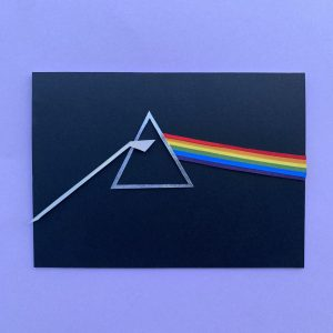 A mixed media piece of the Pink Floyd Dark Side of the Moon triangle with a rainbow line coming out of it