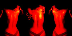 Photographs of a woman's back replicated 3 times under a red light
