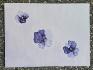 White purple gradient background with three purple violet flowers of various sizes