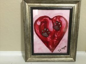 framed red heart with brown pawprints on a pink background