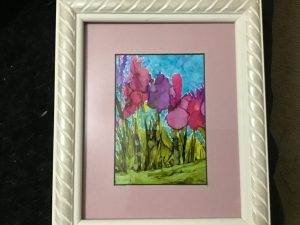 pink and purple flowers with green stems and a wide pink matte frame between the painting and a white frame