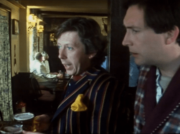 arthur and ford stand with their pints in the pub