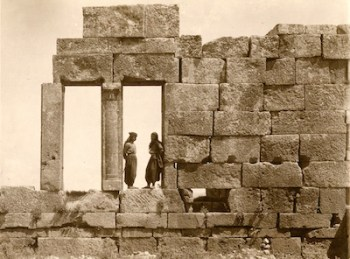 Sepia tone photograph of two people standing in a ruin