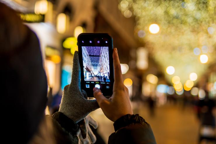 A person holding a smart phone taking a picture of lights at night