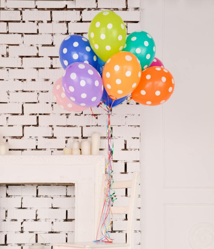 Colorful polka dot balloons against a white brick background