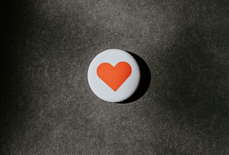 a white pinback button with a red heart