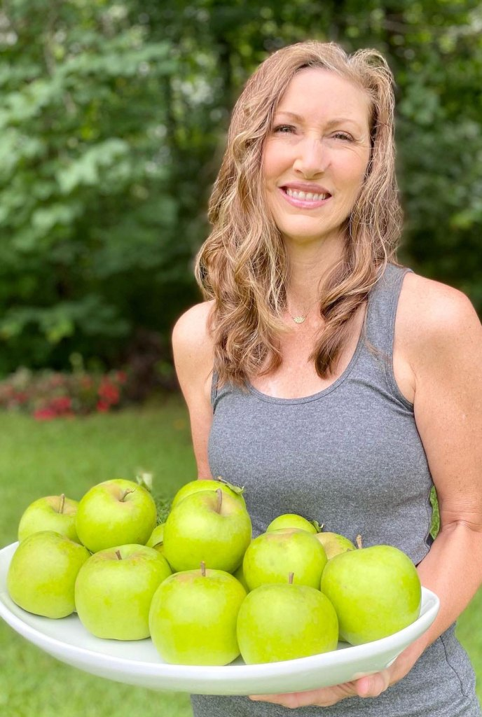 Kimberly Ann Robinson at Vital and Clear holding bowl of apples image