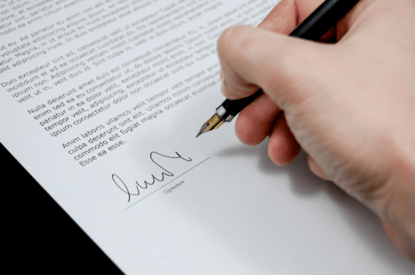 Hand signing a waiver for vaccinations
