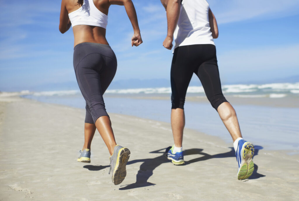 A couple running on the beach. Competitive and active couple.