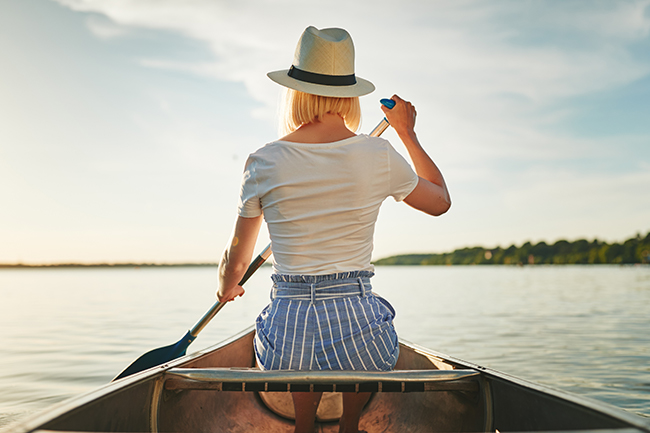 back view of woman canoeing on a sunny lake