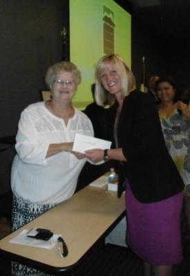 Board members of the Coastal Bend Community Foundation, including (left) Jean Claire Turcotte of Kleberg County, hands (right) Leslie Currie, director of institutional advancement for the Texas A&M Health Science Center Rangel College of Pharmacy, a check for the $5,000 grant to support a Kleberg County Health Fair.