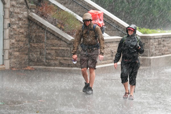 A man and woman searching for shelter in flood conditions