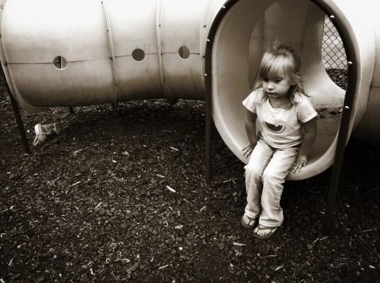 Sad and alone child on the playground.