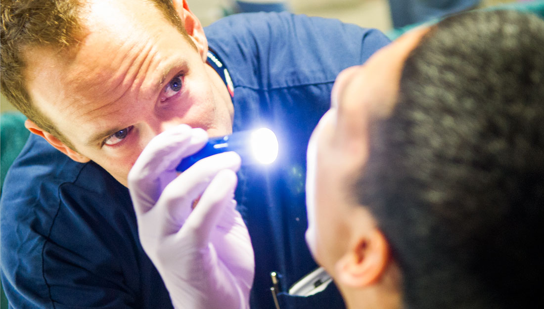 Dentist shinning light into patients mouth