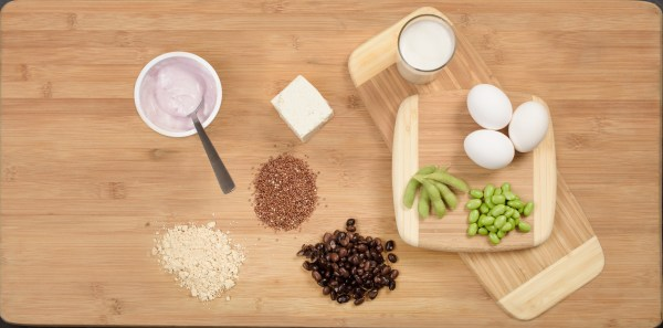 A display of protein-rich foods including eggs, yogurt, peas, and beans.