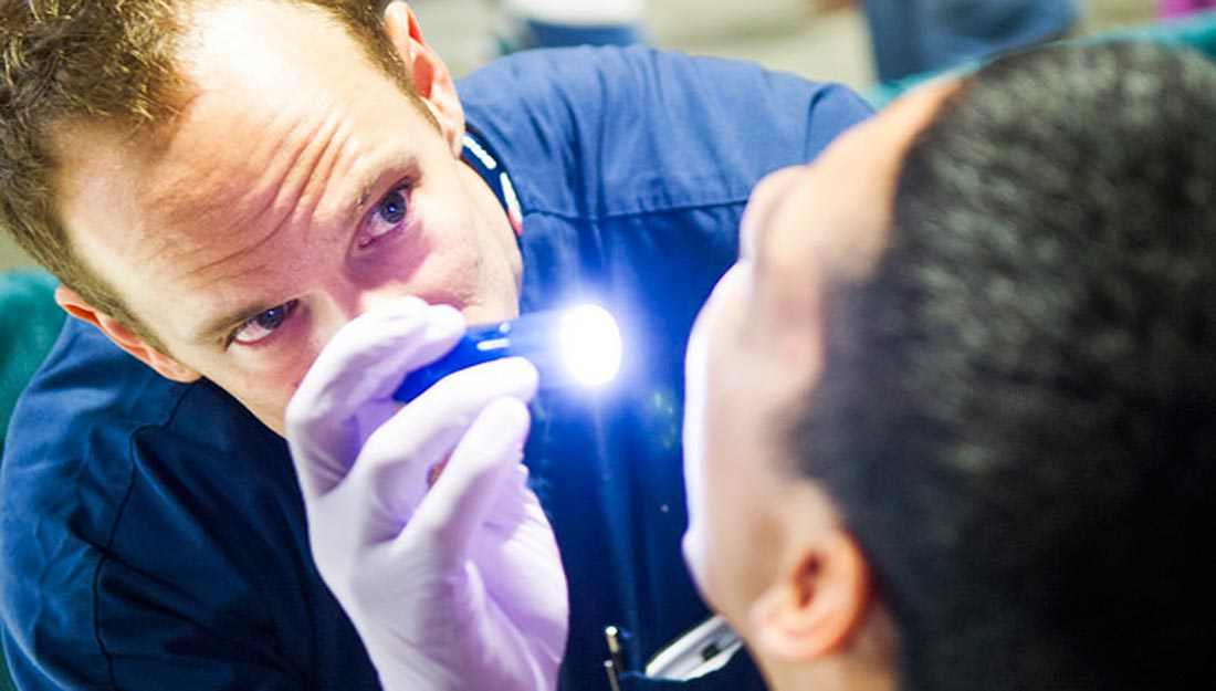 Dentist examining a patient's mouth with a flashlight.