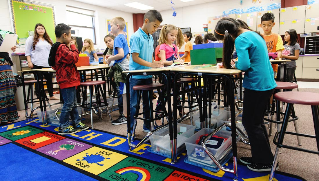 Young children in a classroom using standing desks.