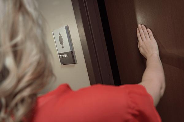 Woman opening bathroom door