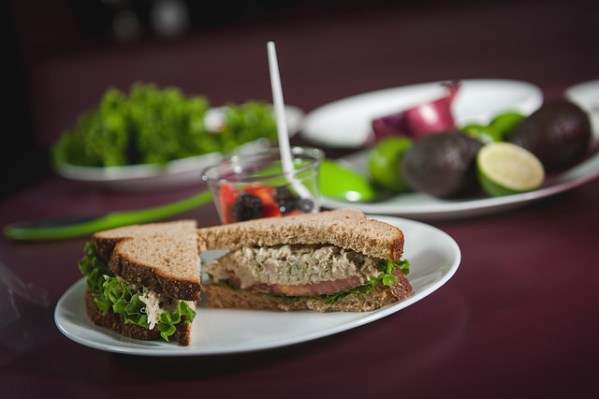 Tuna sandwich sitting on a plate, with chopped vegetables in the background