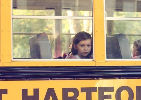 Little girl looking out of a school bus window