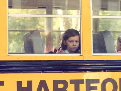 Little girl looking out of a school bus window