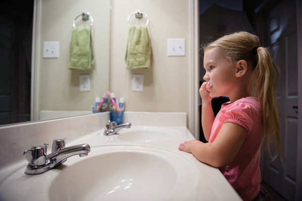 young girl brushing her teeth in front of a bathroom mirror