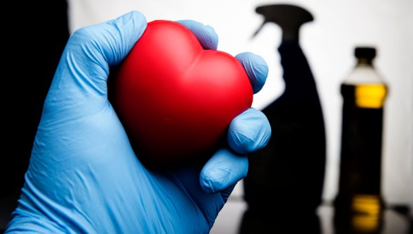 Gloved hand holding up toy heart, background shows chemicals.
