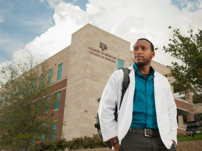 Medical student standing in front of College of Medicine building