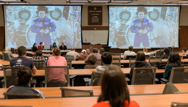 From the ISS, Chancellor speaks from a livestream to a room full of students.