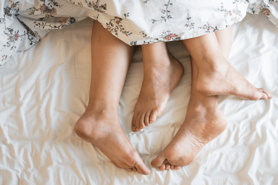 Two pairs of feet peeking out from beneath a blanket on a bed.
