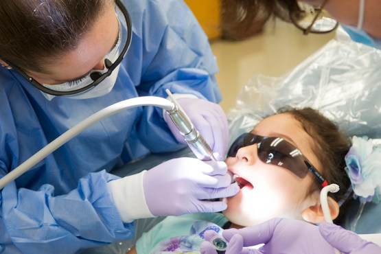 Give Kids a Smile - A dentistry professional performs a dental procedure on a child.