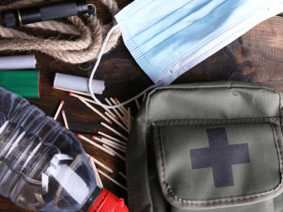 A disaster kit with some contents like matches, water and batteries showing.