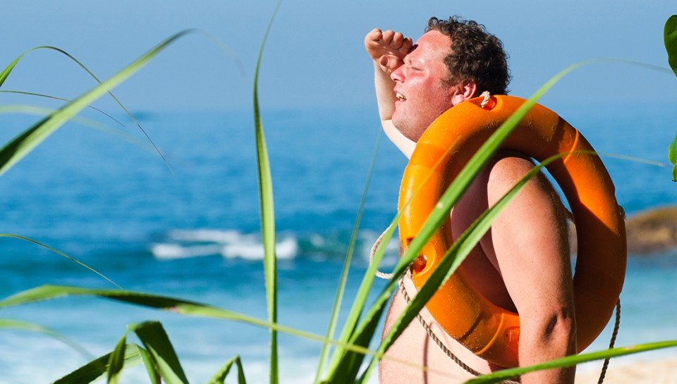 Top 5 injuries and illnesses of the summer-sunburn-a shirtless man with a lifesaver on his shoulder is sunburnt and looking over the ocean