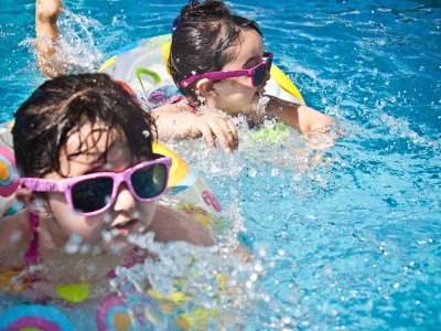 Top 5 injuries and illnesses of the summer-two young girls are swimming with toys and sunglasses on