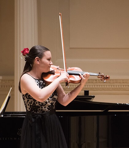 Jillian Khoo is playing a violin in a concert hall near a grand piano.